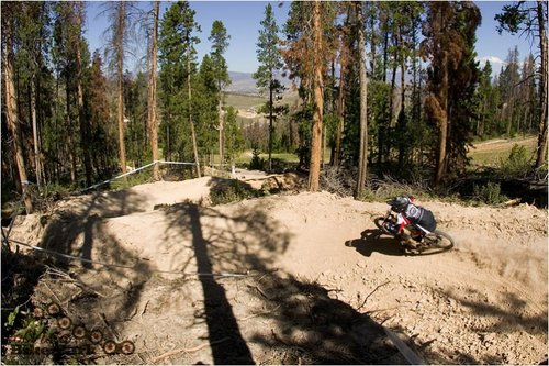 A grom dwarfed by the monster berms on Ashy Larry trail